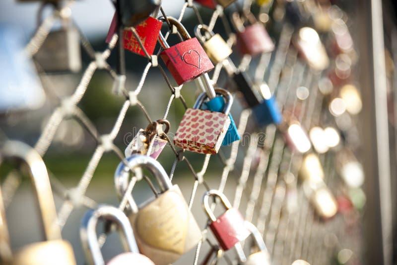 Как обещание влюбленности, любовники закрывают padlocks вдоль моста стоковая фотография