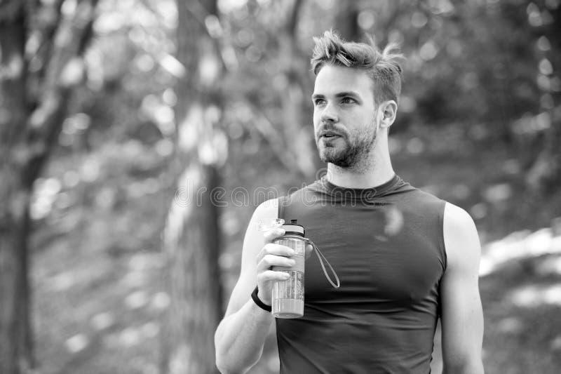 Как раз минута для того чтобы отдохнуть возникновение человека атлетическое держит бутылку с водой Укомплектуйте личным составом  стоковая фотография rf