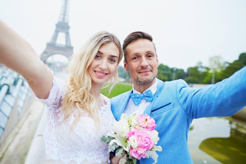 Как раз пожененные пары около Эйфелевой башни в Париже стоковые изображения rf