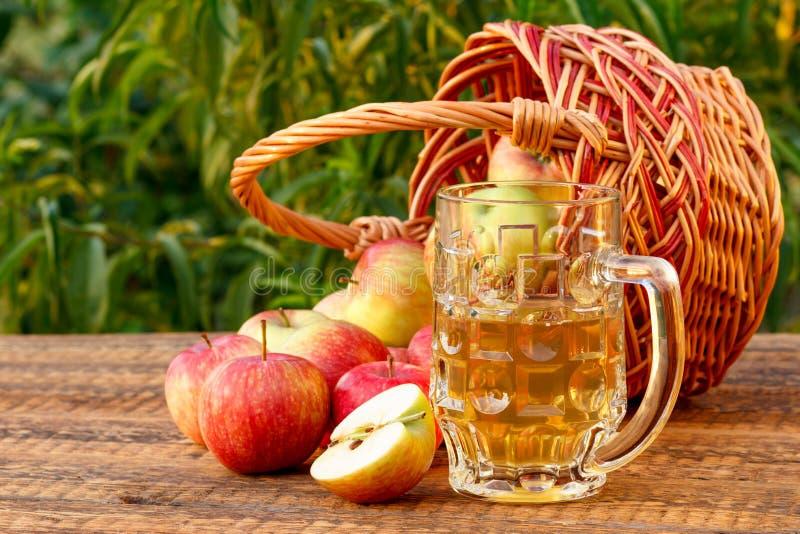 Как раз скомплектовал яблоки в плетеной корзине и яблочный сидр в стеклянном кубке стоковое фото rf