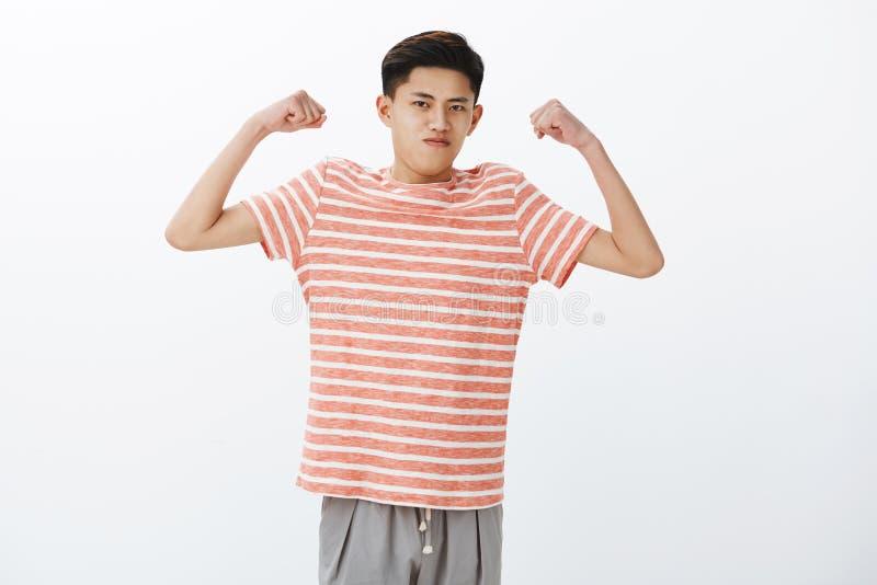 как я смотрю сильным Портрет само-конечно смешных детенышей уменьшает азиатские руки повышения парня для того чтобы показать бице стоковое фото rf