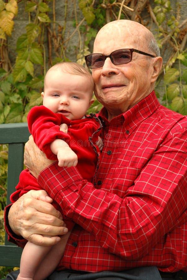 как grandbaby владения укомплектуйте личным составом красную старшую усмешку стоковые изображения rf