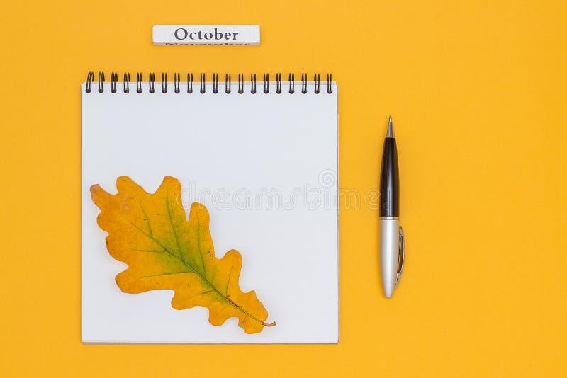 Календарный месяц октябрь, пустой открытый блокнот с ручкой и листья осени на желтой предпосылке Шаблон взгляда сверху модель-мак стоковое фото rf