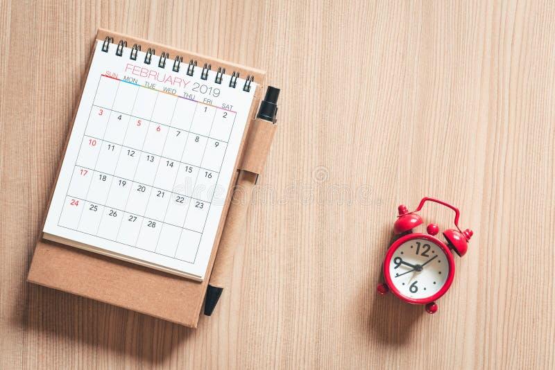 Календарь ежегодный с дозором ручки и кармана встречи на предпосылке таблицы деревянной Встреча расписания для планирования перем стоковое фото