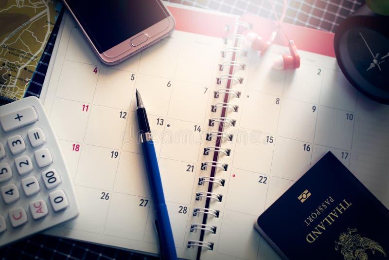 Календарь тетради с ручкой, мобильным телефоном, наушниками, калькулятором, часами, картой и паспортом на столе стоковое изображение rf