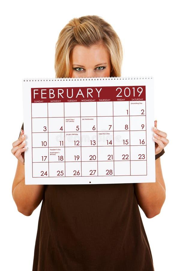 Календарь 2019: Peeking над календарем в феврале стоковые изображения