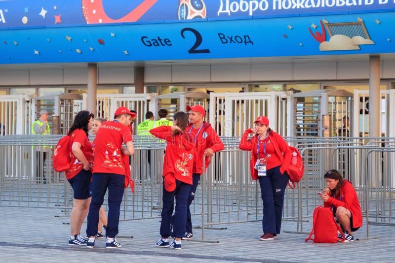 КАЛИНИНГРАД, РОССИЯ - 16-ОЕ ИЮНЯ 2018: Группа в составе молодые волонтеры около современного футбольного стадиона Калининграда стоковое изображение rf