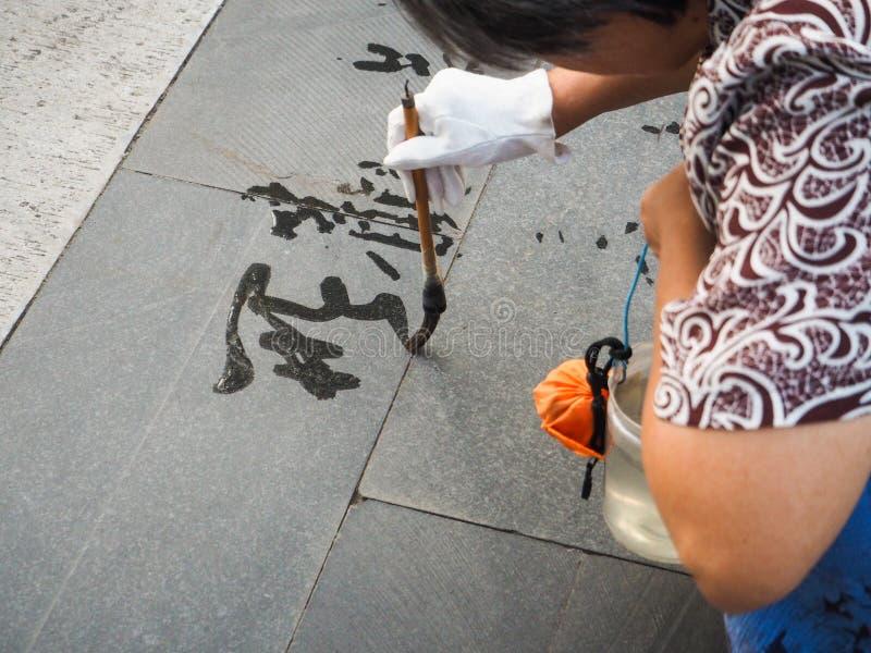 Каллиграфия воды более старой женщины практикуя но должный к жаре стоковые изображения rf