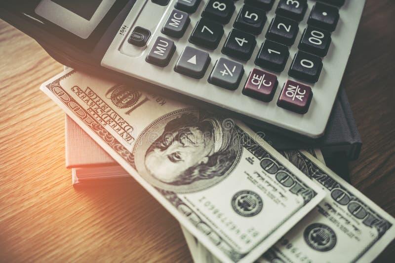 Калькулятор и долларовая банкнота 100 на деревянном столе стоковая фотография rf