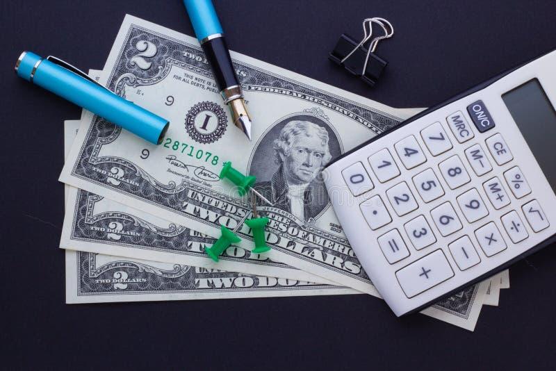 Калькулятор, канцелярские товары и доллары на черной предпосылке, концепция дела стоковая фотография