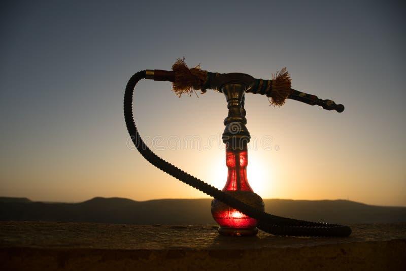 Кальян, традиционное арабское waterpipe, сразу свет захода солнца, внешнее фото Предпосылка горы или силуэты кальяна на заходе со стоковые изображения