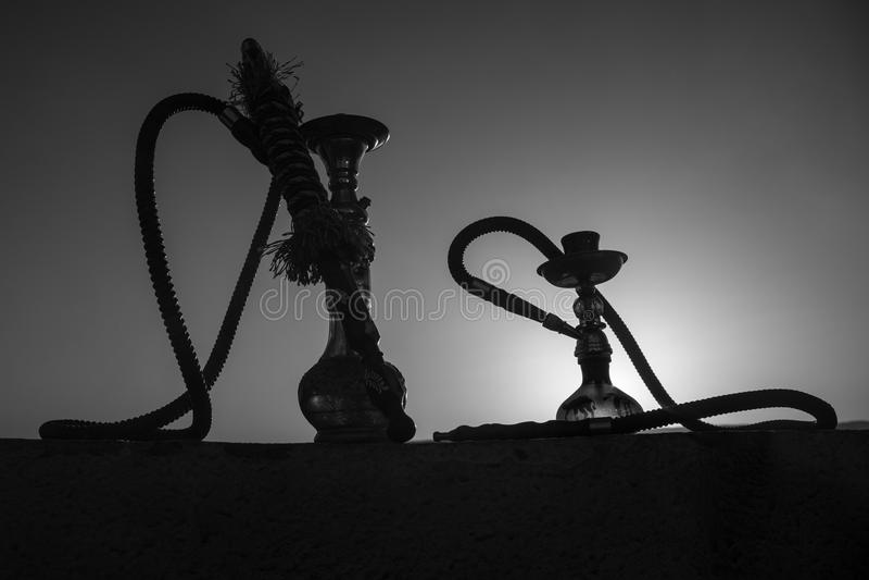 Кальян, традиционное арабское waterpipe, сразу свет захода солнца, внешнее фото Предпосылка горы или силуэты кальяна на заходе со стоковое изображение