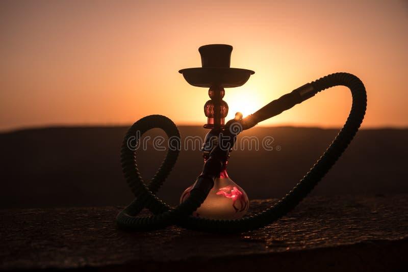 Кальян, традиционное арабское waterpipe, сразу свет захода солнца, внешнее фото Предпосылка горы или силуэты кальяна на заходе со стоковая фотография