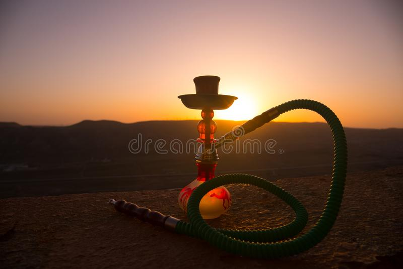 Кальян, традиционное арабское waterpipe, сразу свет захода солнца, внешнее фото Предпосылка горы или силуэты кальяна на заходе со стоковая фотография rf