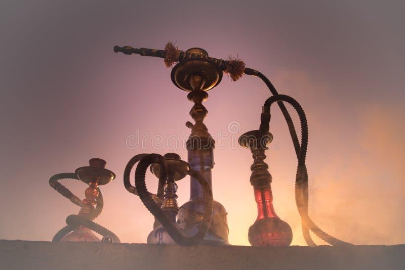 Кальян, традиционное арабское waterpipe, сразу свет захода солнца, внешнее фото Предпосылка горы или силуэты кальяна на заходе со стоковые фотографии rf
