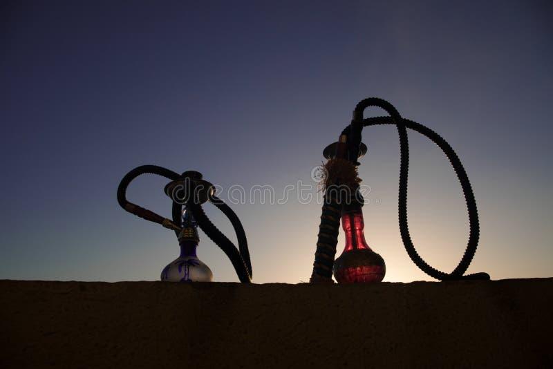 Кальян, традиционное арабское waterpipe, сразу свет захода солнца, внешнее фото Предпосылка горы или силуэты кальяна на заходе со стоковое изображение rf