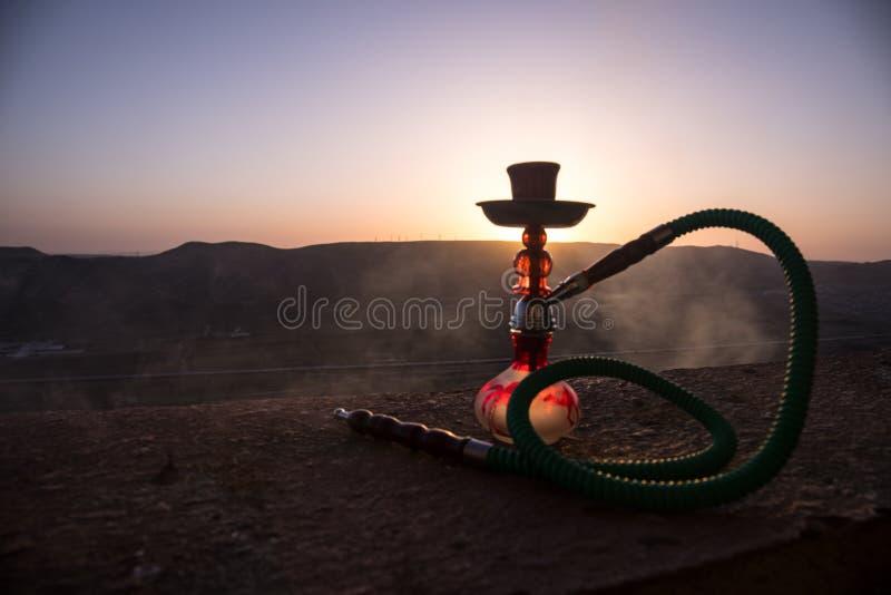 Кальян, традиционное арабское waterpipe, сразу свет захода солнца, внешнее фото Предпосылка горы или силуэты кальяна на заходе со стоковые фото