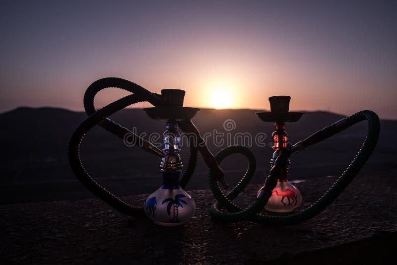Кальян, традиционное арабское waterpipe, сразу свет захода солнца, внешнее фото Предпосылка горы или силуэты кальяна на заходе со стоковое фото rf