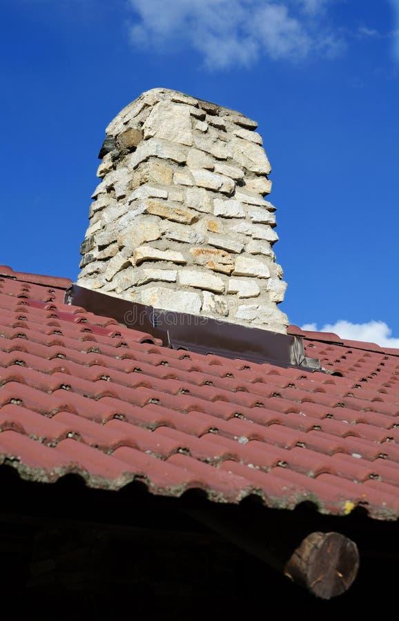 Каменистая печная труба на крыше стоковое изображение