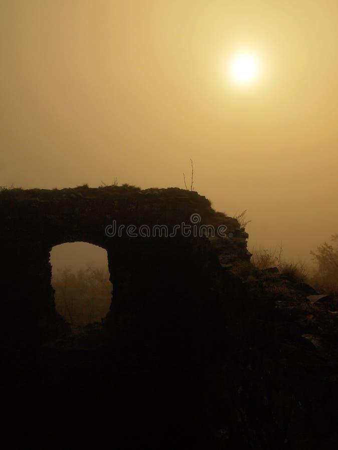 Каменистые руины средневековой башни твердыни на холме Рано утром солнечность спрятанная в тяжелом тумане стоковая фотография rf