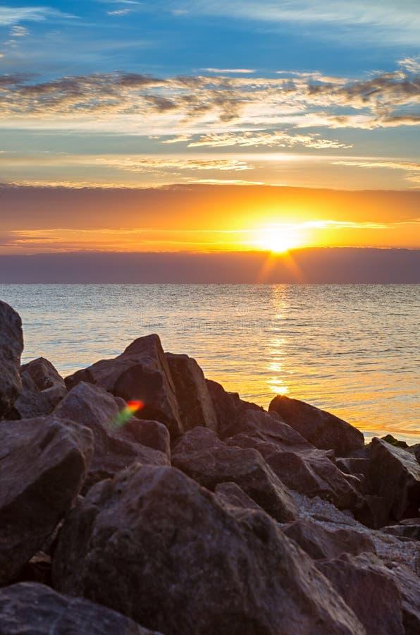 Каменистый берег против моря, заход солнца, облака стоковые фотографии rf