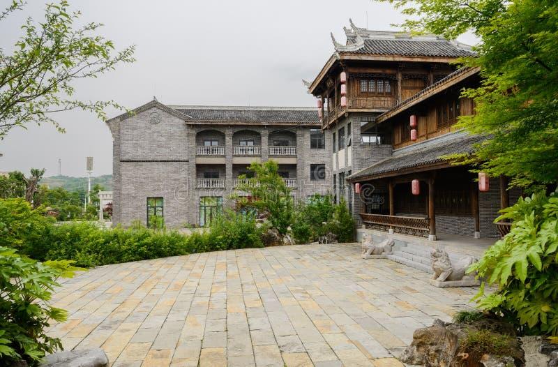 Каменистый грунт перед плитк-настелинным крышу зданием с каменными львами на ent стоковая фотография rf