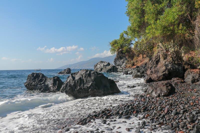 Каменистый пляж с черными камешками лавы Скалистые эксцентричные образования поднимая над поверхностью океана Перерывы прибоя мор стоковые изображения
