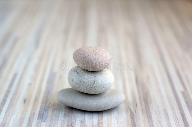 Каменная пирамида из камней на striped предпосылке серой белизны, 3 камня возвышается, простые камни пуаза, сработанность простот стоковые фотографии rf