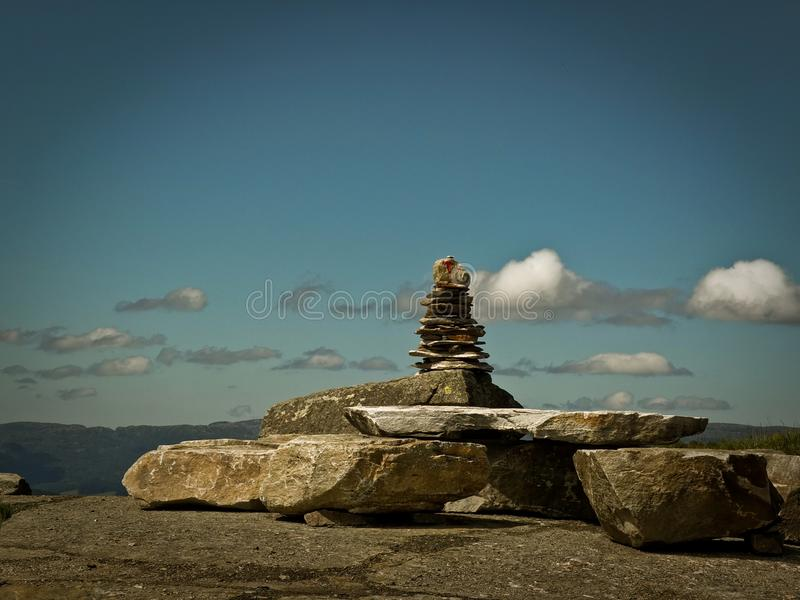 Каменная пирамида любит знак идентификации на тропе на предпосылке зеленой долины стоковая фотография rf