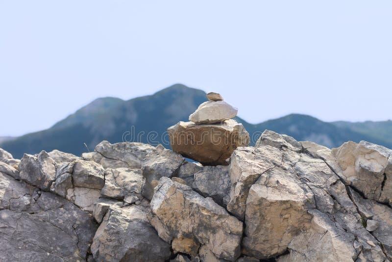Каменная пирамида из камней перед горами и небом стоковая фотография rf
