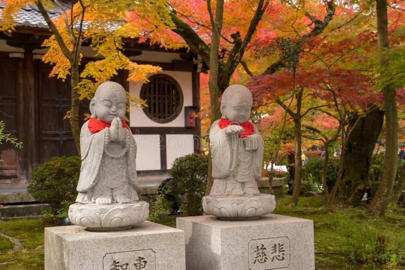 Каменная скульптура послушника 2 под деревьями осени стоковая фотография rf