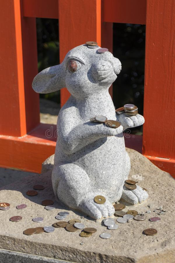 Каменная статуя кролика с некоторыми монетками, касаясь кролику принесет удачи стоковые изображения rf