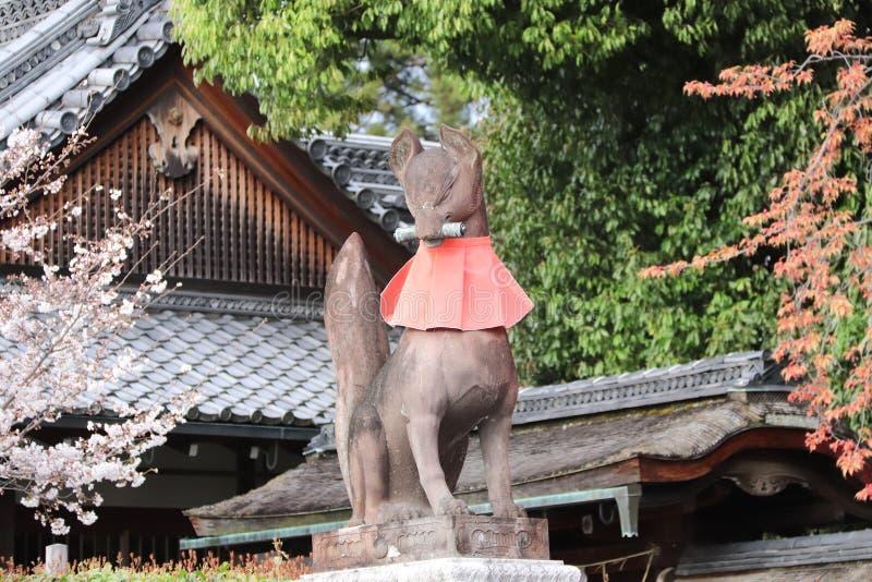 Каменная статуя лисы Inari в святыне Fushimi Inari, Киото, Японии стоковое фото