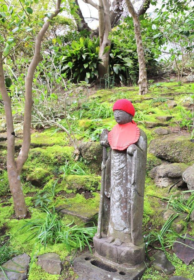 Каменная статуя Jizo в связанной шляпе, Miyajima, Японии стоковое изображение rf