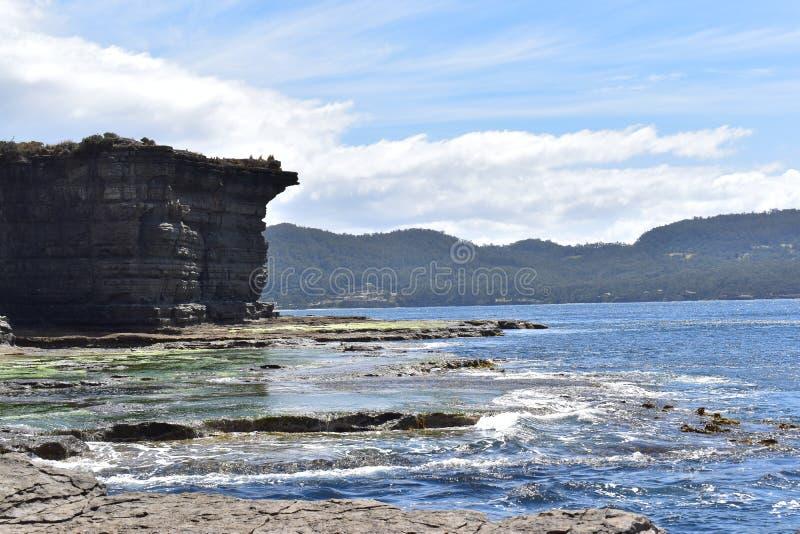 Каменная стена в пляже Тасмании с солнечным днем стоковая фотография