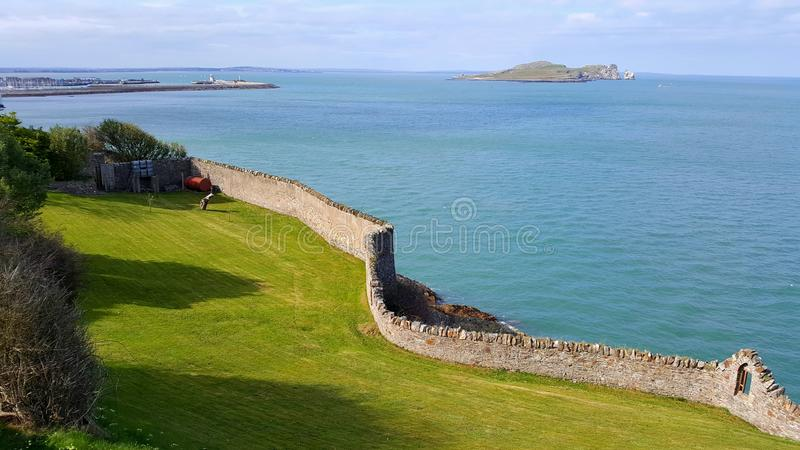 Каменная стена на морском побережье с островом на заднем плане стоковое фото rf