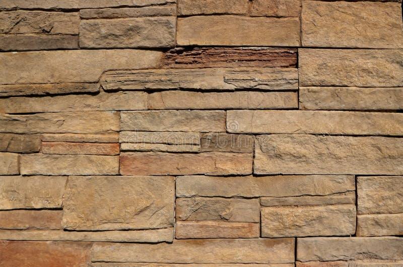 Каменная стена плакирования для деревенского экстерьера, сделанная штабелированных естественных коричневых утесов с скачками форм стоковые фото