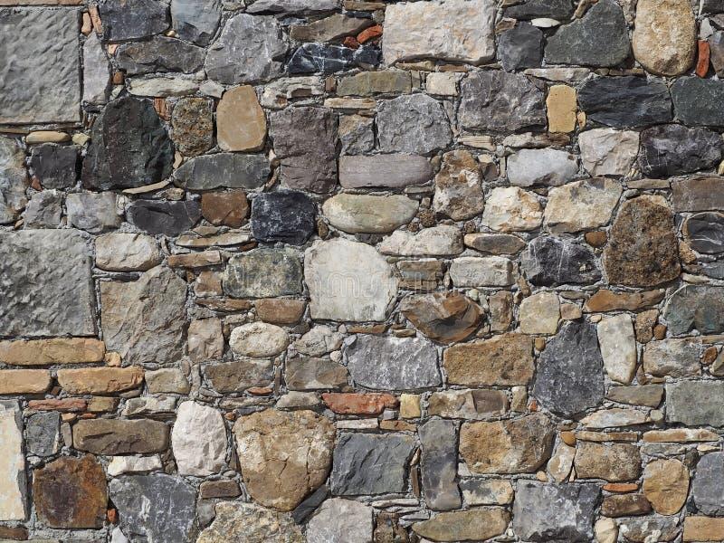 Каменная стена сделанная скачками естественных утесов различных размеров, кирпичей и слябов стоковое изображение
