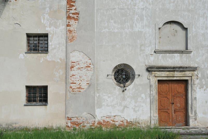 Каменная стена со старой деревянной дверью и небольшим окном стоковое изображение rf