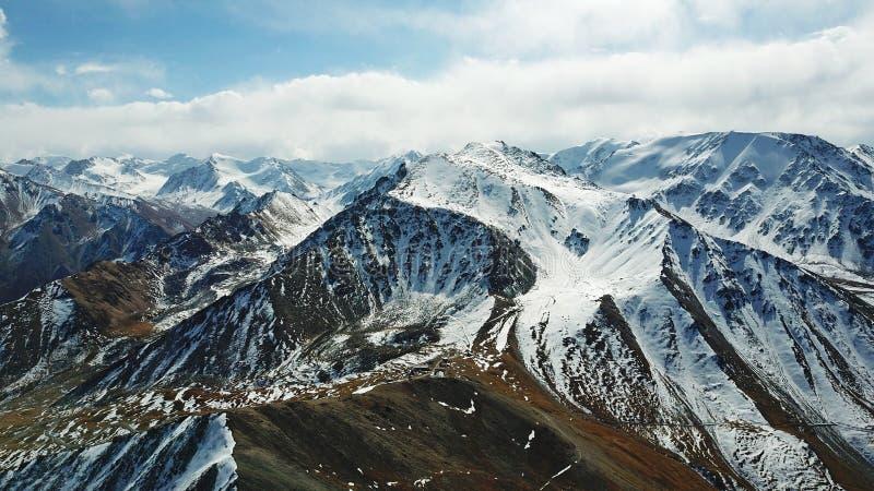 Каменные и снег-покрытые горы синь заволакивает небо Стрельба с трутнем стоковая фотография rf