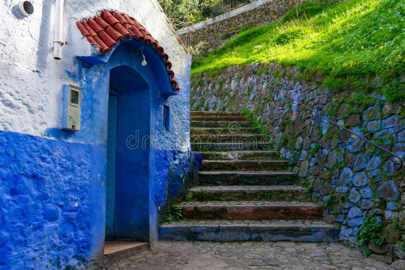 Каменные лестницы вверх по холму рядом с голубым коттеджем в Chefchaouen Марокко стоковые фото