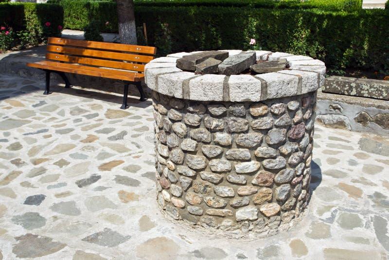 Каменные фонтан и деревянная скамья стоковое изображение rf