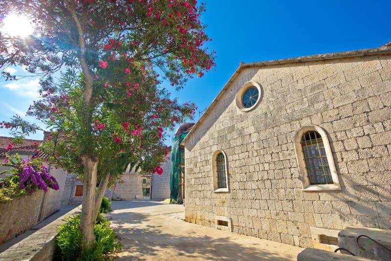 Каменные церковь и цветки острова Hvar стоковое изображение