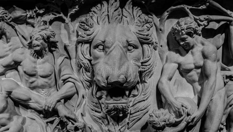 Каменный барельеф льва и богов стоковое фото