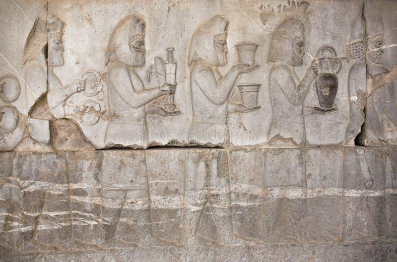 Каменный барельеф при древние люди держа еду и окаимленные оружия в Persepolis, Иране стоковые фотографии rf