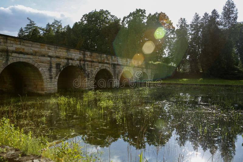 Каменный мост над перерастанными пирофакелами withlens пруда стоковые изображения