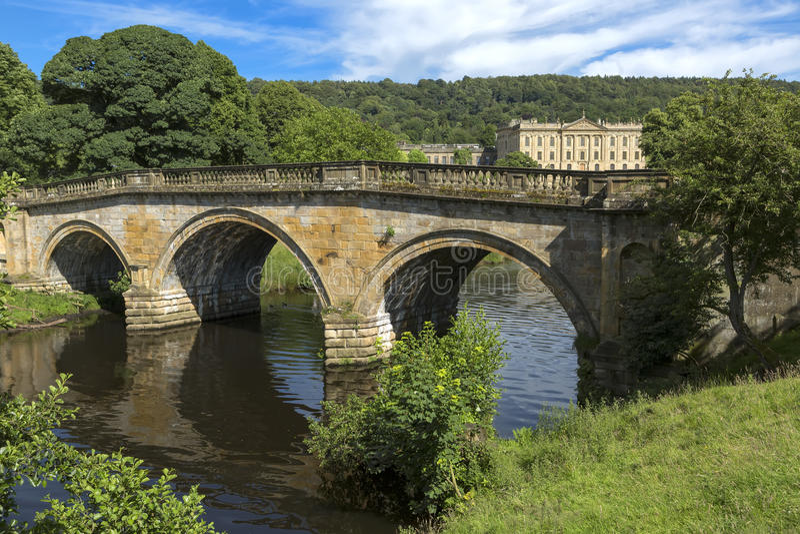 Каменный мост дороги над рекой Derwent на имуществе дома Chatsworth, Дербишире стоковая фотография rf