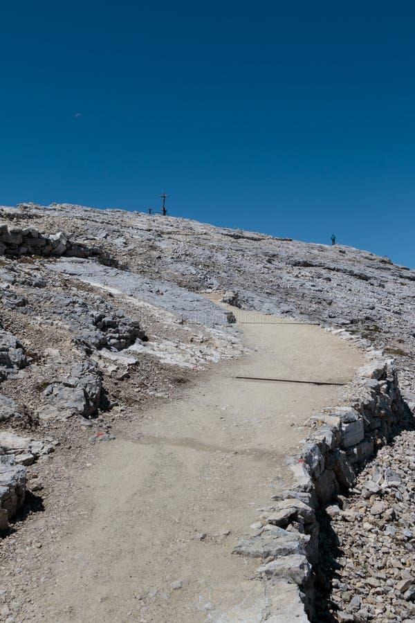 Каменный путь среди неурожайных гор, деревянного христианского креста и Wo стоковые фотографии rf