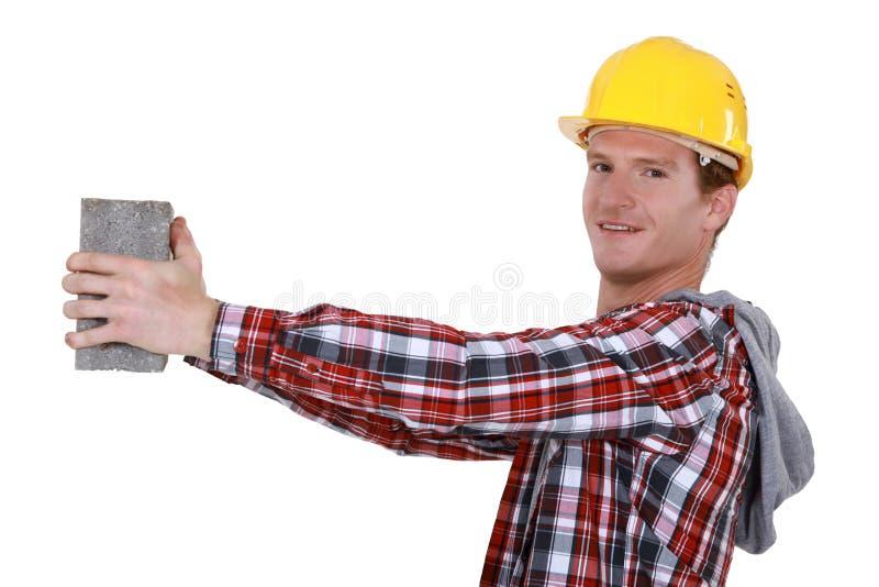 Каменщик держа кирпич стоковая фотография rf