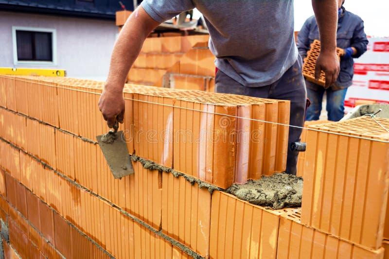 Каменщик с кирпичом на строительной площадке стоковые изображения rf